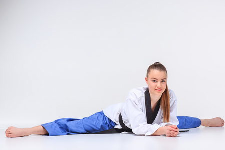 The karate girl in white kimono and black belt training karate over gray background. Stretching before exercise twine