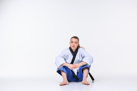 martial arts woman: The karate girl in white kimono and black belt sitting over white background.