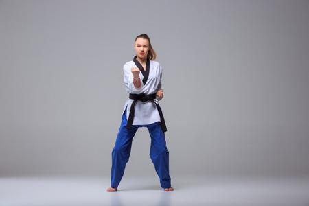 The karate girl in white kimono and black belt training karate over gray background.