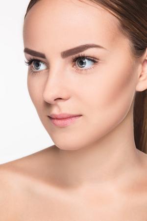 masaje facial: Hermoso rostro de mujer joven con la piel limpia fresca de cerca aislado en blanco. Retrato de belleza. Piel fresca perfecta. Pura belleza del modelo. Juventud y Cuidado de la piel Concept
