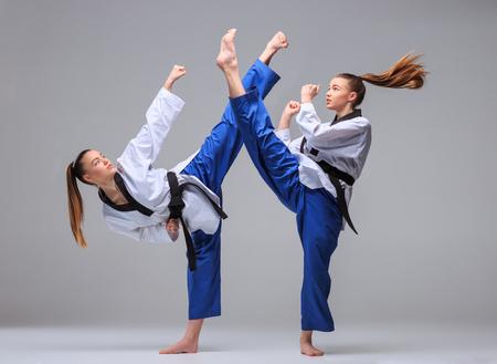 patada: El collage de la muchacha del karate en el kimono blanco y negro de karate de entrenamiento cinta sobre fondo gris. Foto de archivo