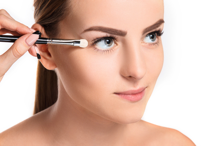 visagiste: Beautiful female eyes with make-up and brush on white
