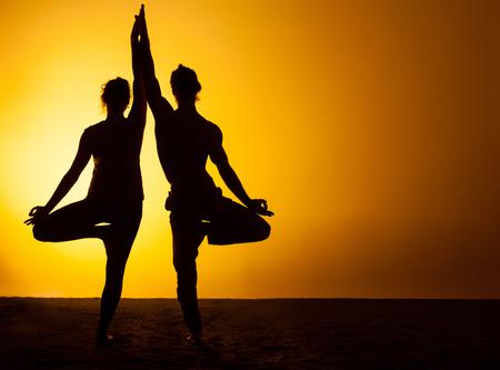 Les deux silhouettes de personnes pratiquant le yoga dans la lumière du soleil couchant Banque d'images