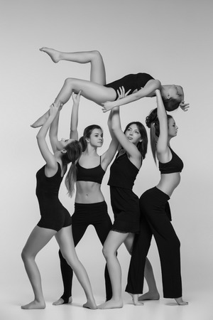 colorless: The group of modern ballet dancers posing on gray background. The black and white or colorless photo Stock Photo