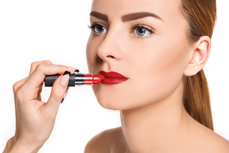 pomade: Beautiful female lips with make-up and red pomade on white. Makeup artist working process