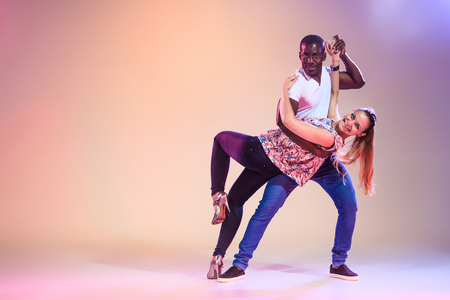 nude girl young: Young couple dances social Caribbean Salsa, studio shot on lilac background. Positive human emotions. The black african and caucasian models