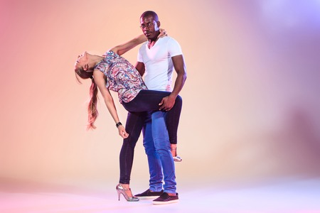 young girl nude: Young couple dances social Caribbean Salsa, studio shot on lilac background. Positive human emotions. The black african and caucasian models