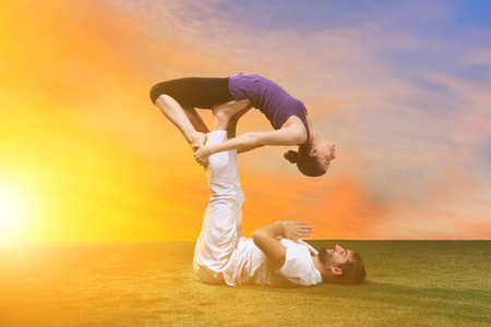 man health: The two people doing yoga exercises against sunset sky