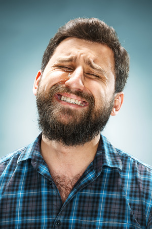 The crying man with tears on face closeup on blue background