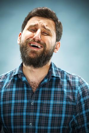 volto uomo: L'uomo piangere con le lacrime sul viso del primo piano su sfondo blu Archivio Fotografico