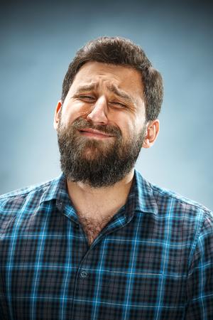 visage homme: L'homme qui pleure des larmes sur le visage gros plan sur fond bleu