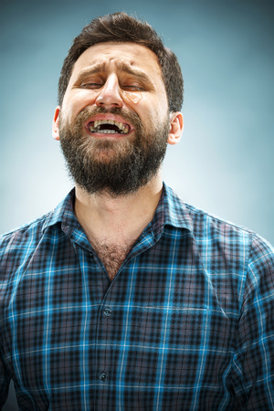 lagrimas: El hombre llorando con lágrimas en la cara de cerca sobre fondo azul