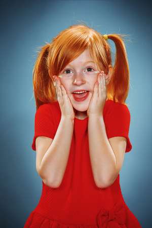 red hair girl: The beautiful portrait of a  surprised little girl with red hair in red dress on blue