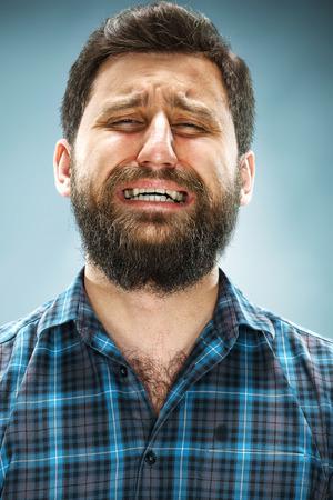 occhi tristi: L'uomo che piange sul viso alzato su sfondo blu Archivio Fotografico