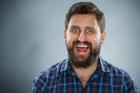 headshot: Closeup headshot portrait, happy  ecstasy handsome man in blue shirt on blue background