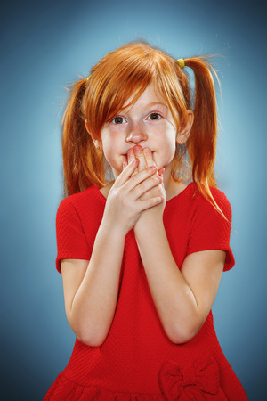 The beautiful portrait of a surprised little girl with red hair in red dress on blue