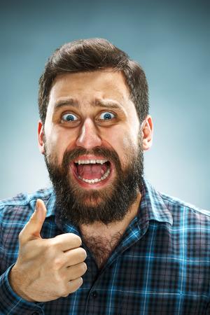ecstasy: Retrato de vieron de cerca, hombre guapo �xtasis feliz en camisa azul sobre fondo azul Foto de archivo