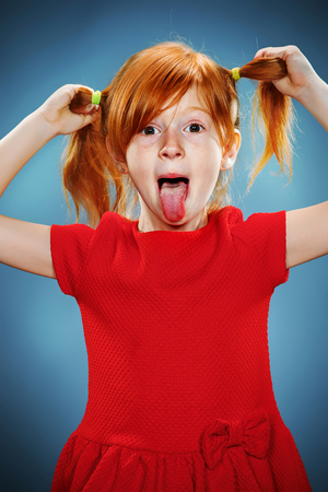 tongues: The beautiful portrait of a little girl with his tongue hanging out with red hair in red dress on blue Stock Photo