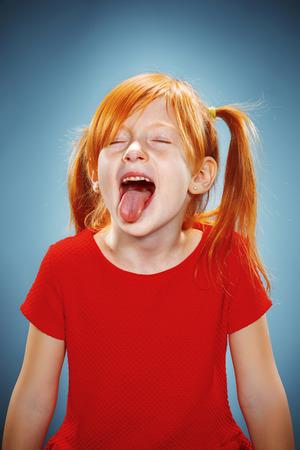 Het mooie portret van een meisje met zijn tong opknoping uit met rode haren in rode jurk op blauwe
