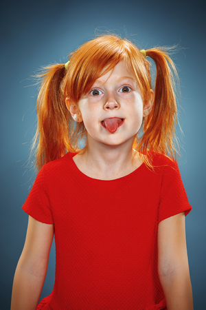 hang out: The beautiful portrait of a little girl with his tongue hanging out with red hair in red dress on blue Stock Photo