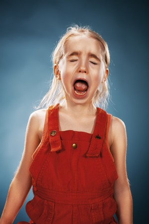 The portrait of a little girl in red dress on blue background. She is crying