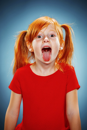 The beautiful portrait of a little girl with his tongue hanging out with red hair in red dress on blue Stockfoto