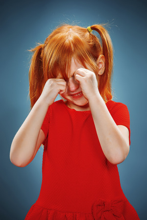 CLOSE UP FACE: The portrait of a little girl in red dress on blue background. She is crying