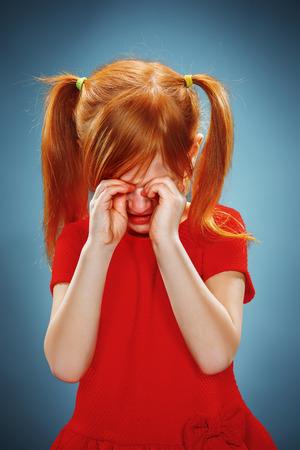 petite fille triste: Le portrait d'une petite fille en robe rouge sur fond bleu. Elle pleure