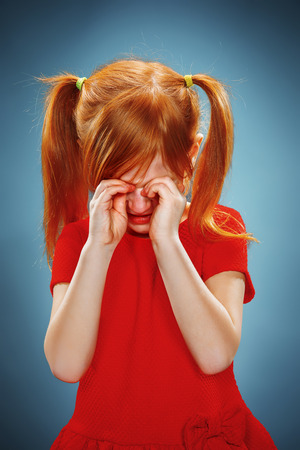 face close up: The portrait of a little girl in red dress on blue background. She is crying