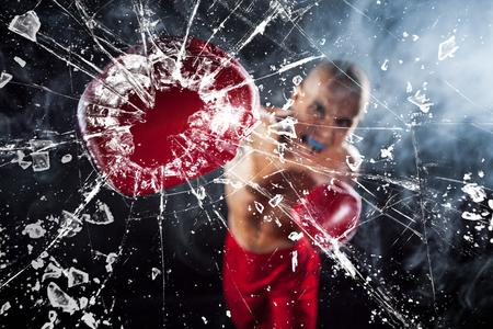 Il pugile schiacciare un bicchiere. Il giovane atleta di sesso maschile kickboxing su uno sfondo di fumo blu