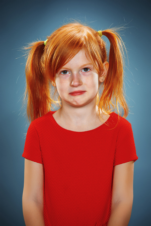 The beautiful portrait of a thoughtful little girl with red hair in red dress on blue