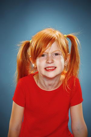 petite fille triste: Le beau portrait de m�content et m�contents petite fille en robe rouge sur bleu