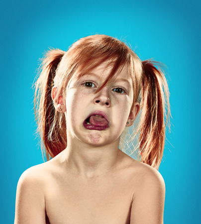 one child: The beautiful portrait of  displeased and disaffected little girl  on blue Stock Photo