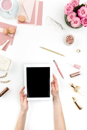 De vrouwelijke handen en tablet tegen mode vrouw objecten op wit. Concept van vrouwelijke mockup en comfortabele vrouwelijke werkplek Stockfoto