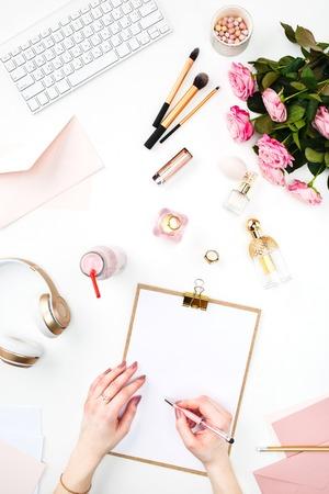 Las manos de una mujer escribiendo en contra de la mujer de moda objetos en blanco. Concepto de maqueta femenina y el lugar de trabajo femenina cómoda Foto de archivo