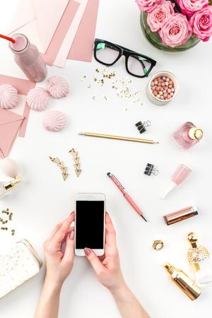 De vrouwelijke handen en slimme telefoon tegen mode vrouw objecten op wit. Concept van vrouwelijke mockup en comfortabele vrouwelijke werkplek
