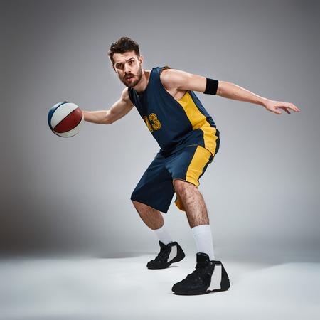 baloncesto: Retrato de cuerpo entero de un jugador de baloncesto con una pelota contra el fondo gris del estudio