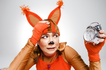 role models: Young woman in the image of red squirrel with horror looking at  alarm clock. The business concept of syndrome squirrel in a wheel