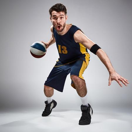Full length portret van een basketbalspeler met een bal tegen een grijze achtergrond studio Stockfoto