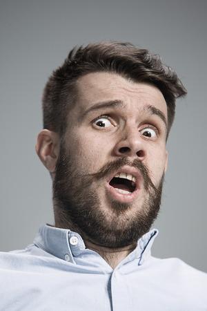 青いシャツを着た男は怖がっています。灰色の背景の上