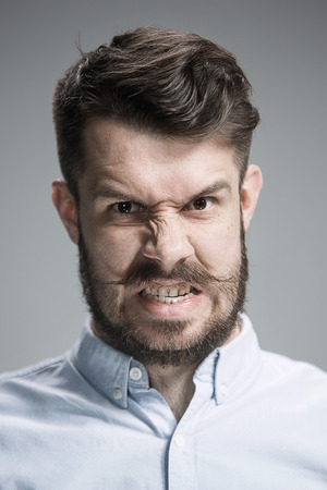 hiss: Close up of face of angry man on gray background
