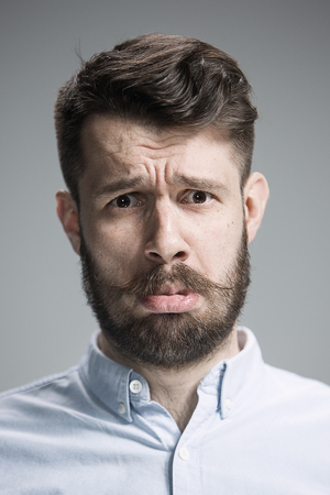 grieved: Close up of face of discouraged man on gray background