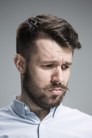 discouraged: Close up of face of discouraged man on gray background