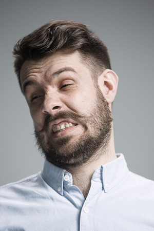 disgusted: The portrait of disgusted man on gray Stock Photo