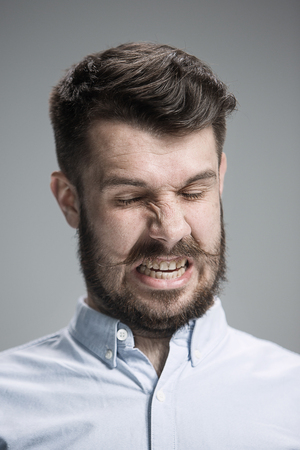 is disgusted: The portrait of disgusted man on gray Stock Photo