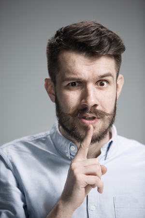 cautious: Man wearing a blue shirt is looking wary. Over gray background Stock Photo