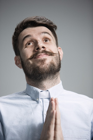 imploring: Man wearing a blue shirt is looking imploring. Over gray background Stock Photo