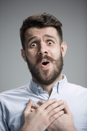 Man wearing a blue shirt is looking imploring. Over gray background Stock Photo