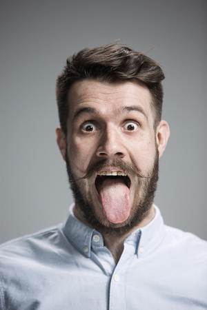 denote: The tongue hanging out man on the gray background Stock Photo