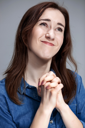 imploring: Woman wearing a blue shirt is looking imploring. Over gray background